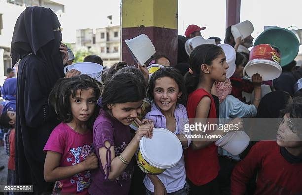 Syrians wait with their buckets as The Foundation for Human Rights and Freedoms And Humanitarian Relief gives hot meal at Martyrs Square as the...