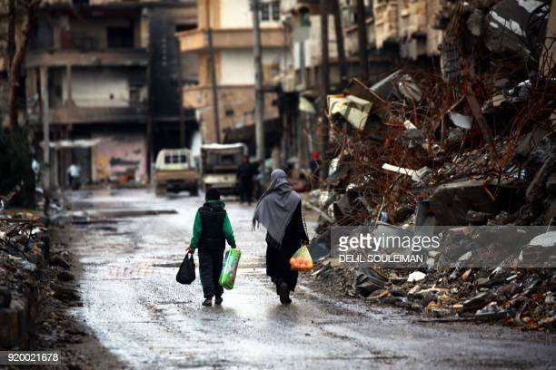 TOPSHOT Syrians walk along a destroyed street in Raqa the former de facto capital of the Islamic State group on February 18 2018 / AFP PHOTO / DELIL...
