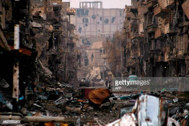 Syrians walk along a severely damaged road in the northeastern city of Deir Ezzor on January 4, 2014. Syrian rebels have united to kill and capture...