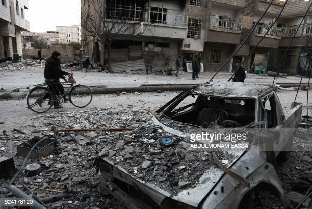 TOPSHOT Syrians walk along a street covered in debris from shelling in Arbin in the rebelheld enclave of Eastern Ghouta on February 25 2018 New...
