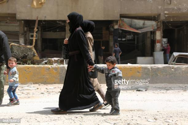 Syrians walk along a street in the former rebelheld Syrian town of Douma on the outskirts of Damascus on April 19 five days after the Syrian army...