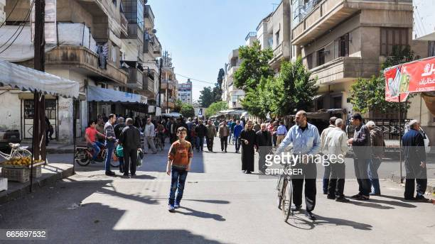 Syrians walk along an openair market in a street in the country's central and third largest city of Homs on April 7 2017 / AFP PHOTO / STRINGER