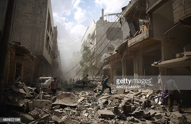 Syrians walk amid the rubble of destroyed buildings following reported air strikes by regime forces in the rebelheld area of Douma east of the...
