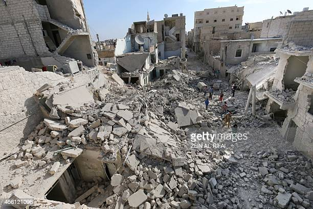 Syrians walk amidst destroyed buildings following reportedly Syrian government forces barrel bomb attacks in the northern city of Aleppo on September...