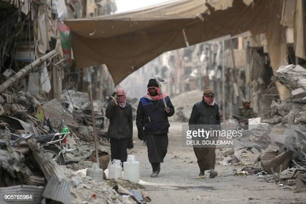 TOPSHOT Syrians walk amidst the debris of destroyed buildings in the northern Syrian city of Raqa on January 11 2018 after a huge military operation...
