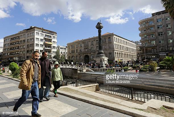 Syrians walk at Marjeh Square in the capital Damascus on March 16 2016 / AFP / LOUAI BESHARA