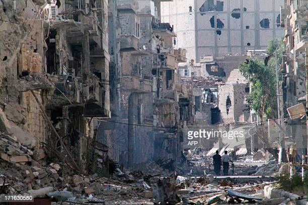 Syrians walk down a destroyed street in the centre of Syria's northeastern city of Deir Ezzor on June 27 2013 More than 100000 people have been...