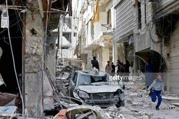 Syrians walk in a destroyed street in the Eastern Ghouta town of Saqba on March 18 2018 as civilians return to the area after regime forces took...