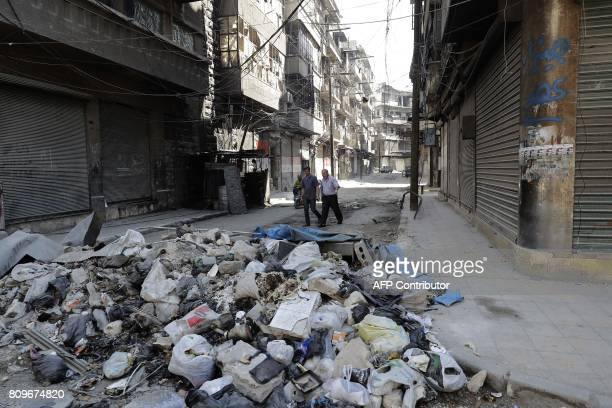 Syrians walk in Aleppo's Kallase industrial neighbourhood on July 5 2017 Six months after Syria's army captured the country's onetime economic...