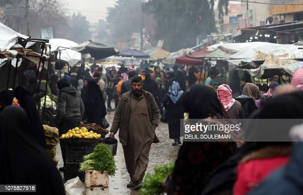 Syrians walk in an open market in the northern town of Manbij on the Turkish border which is controlled since 2016 by an alliance of Kurdish and Arab...