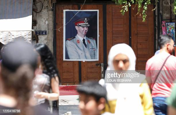 Syrians walk in old Damascus in front of a portrait of Syrian President Bashar alAssad on June 16 2020 The Caesar Syria Civilian Protection Act of...
