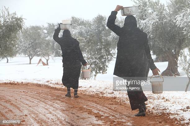 Syrians walk on a muddy road after receiving food aid in plastic buckets at a tent city as it snows in the Azaz town of Aleppo Syria on December 21...