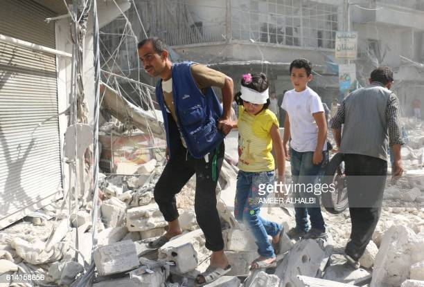 TOPSHOT Syrians walk over rubble following air strikes on the rebelheld Fardous neighbourhood of the northern embattled Syrian city of Aleppo on...