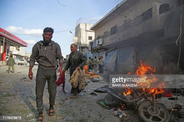 Syrians walk past a burning motorcycle at the site of a car bomb explosion in the northern Syrian Kurdish town of Tal Abyad, on the border with...