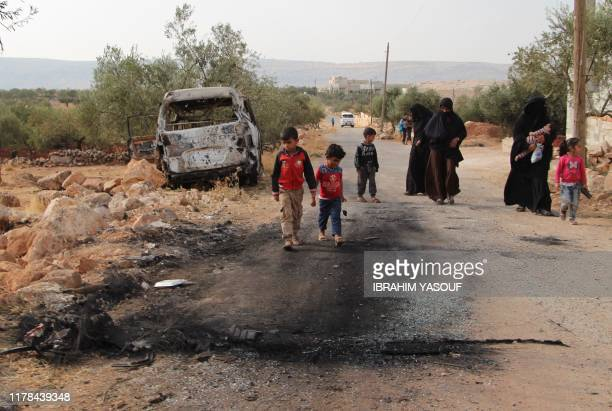 Syrians walk past a damaged van at the site of helicopter gunfire which reportedly killed nine people near the northwestern Syrian village of Barisha...