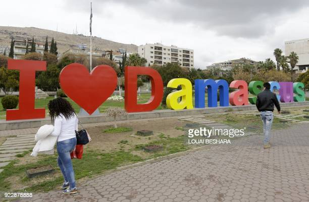Syrians walk past an 'I love Damascus' installation the centre of the Syrian capital Damascus on February 22 2018 / AFP PHOTO / LOUAI BESHARA