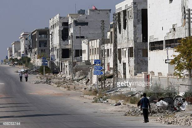 Syrians walk past destroyed buildings in Aleppo's industrial area in the government controlled side of the wartorn northern Syrian city on November...