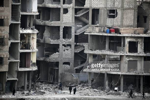 Syrians walk past destroyed buildings in Arbin in the rebelheld enclave of Eastern Ghouta on February 25 2018 New regime air strikes and heavy...