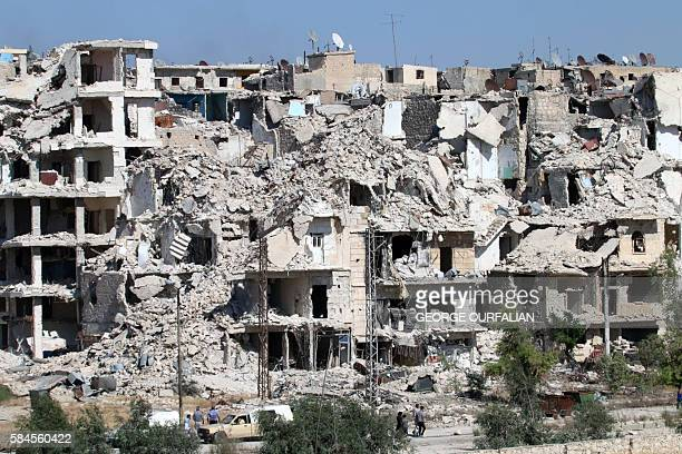 Syrians walk past heavily damaged buildings in the neighbourhood of Bani Zeid on Aleppo's northern outskirts on July 29 as people come back to the...