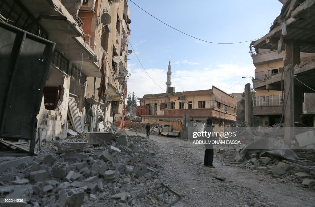 Syrians walk past heavily-damaged buildings down a street covered with rubble next to a destroyed hospital that was hit by a reported regime air strike in the rebel-held enclave of Hamouria in the Eastern Ghouta near Damascus on February 21, 2018. /