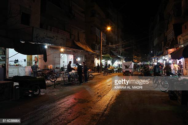 Syrians walk past market stalls on a lit street on March 6 2016 in an eastern rebel held district of the city of Aleppo as the area was reconnected...