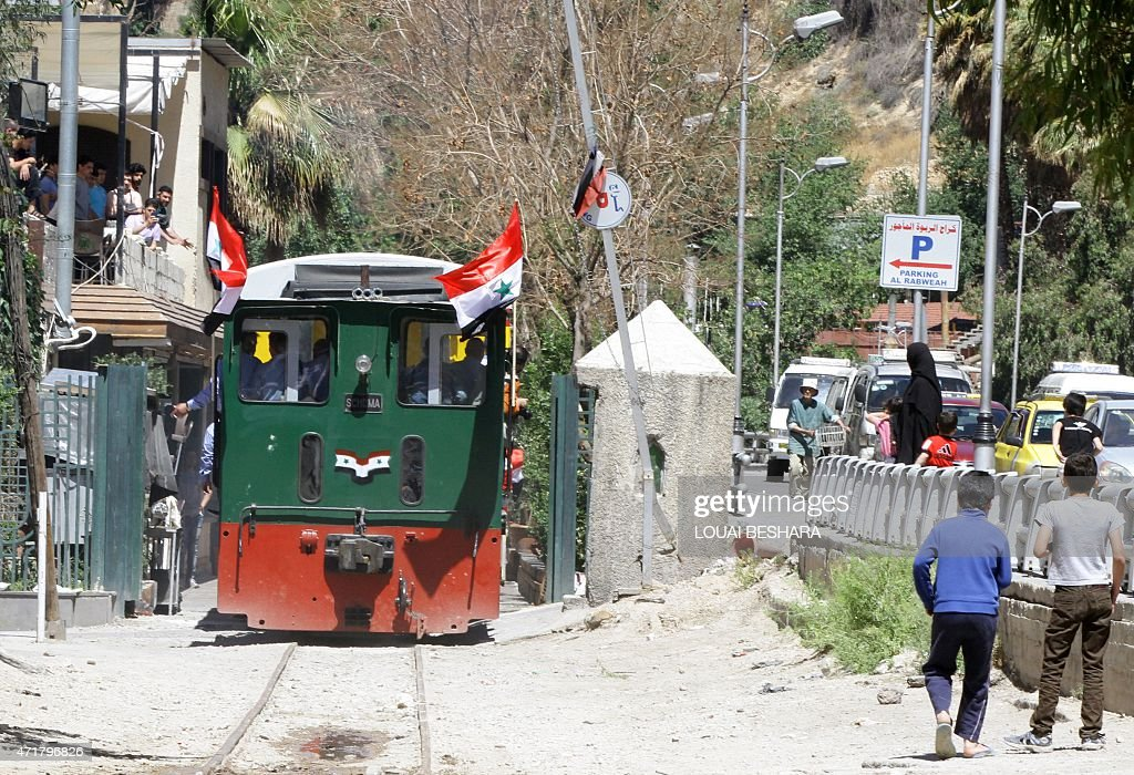Syrians watch on as the tourist train in Damascus passes, following the re-opening ceremony of the rail route between two neighbourhoods in the Syrian capital, Raboeh and Dumar, on May 1, 2015.