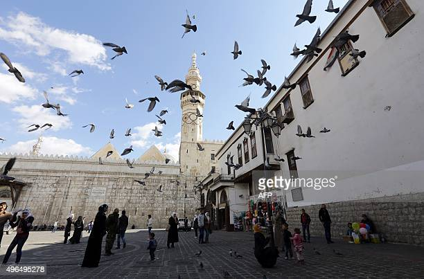 Syrians watch pigeons flying outside the Umayyad Mosque in the Syrian capital Damascus on November 10 2015 / AFP / LOUAI BESHARA