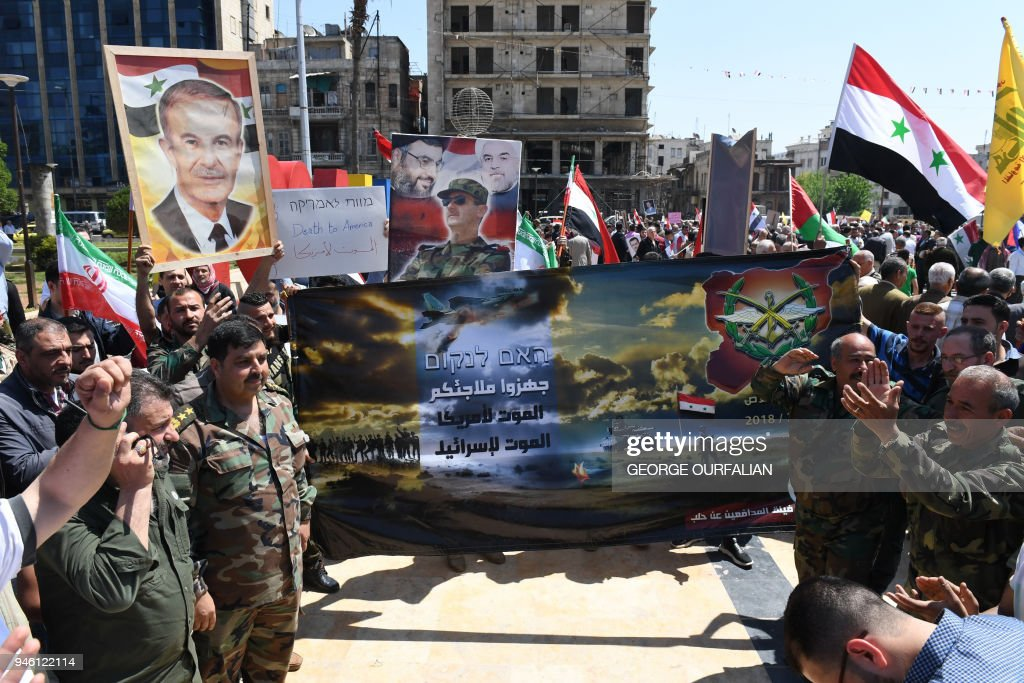 Syrians wave the national flag and carry portraits of President Bashar al-Assad as they gather in Aleppo's Saadallah al-Jabiri square on April 14, 2018, to condemn the strikes carried out by the United States, Britain and France against the Syrian regime. / AFP PHOTO / George OURFALIAN