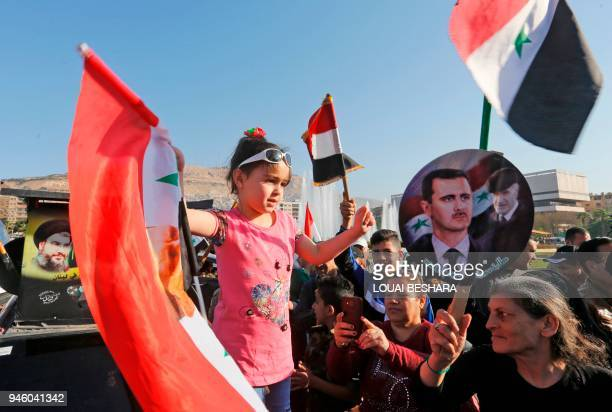 TOPSHOT Syrians wave the national flag and portraits of President Bashar alAssad as they gather at the Umayyad Square in Damascus on April 14 to...
