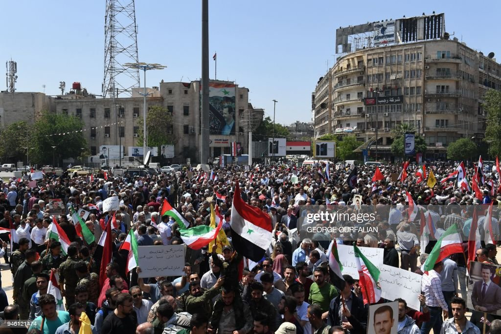 Syrians wave the national flag and portraits of President Bashar al-Assad as they gather in Aleppo's Saadallah al-Jabiri square on April 14, 2018, to condemn the strikes carried out by the United States, Britain and France against the Syrian regime. / AFP PHOTO / George OURFALIAN