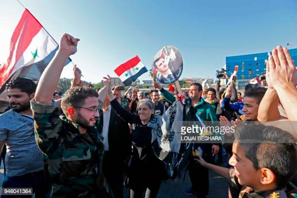 TOPSHOT Syrians wave the national flag and wave portraits of President Bashar alAssad as they gather at the Umayyad Square in Damascus on April 14 to...