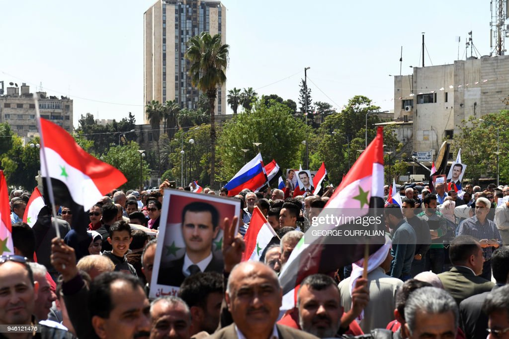 Syrians wave the national flag and wave portraits of President Bashar al-Assad as they gather in Aleppo's Saadallah al-Jabiri square on April 14, 2018, to condemn the strikes carried out by the United States, Britain and France against the Syrian regime. / AFP PHOTO / George OURFALIAN