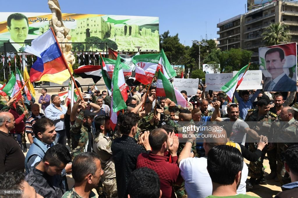 Syrians wave the Russian and Iranian flags and carry portraits of President Bashar al-Assad as they gather in Aleppo's Saadallah al-Jabiri square on April 14, 2018, to condemn the strikes carried out by the United States, Britain and France against the Syrian regime. / AFP PHOTO / George OURFALIAN
