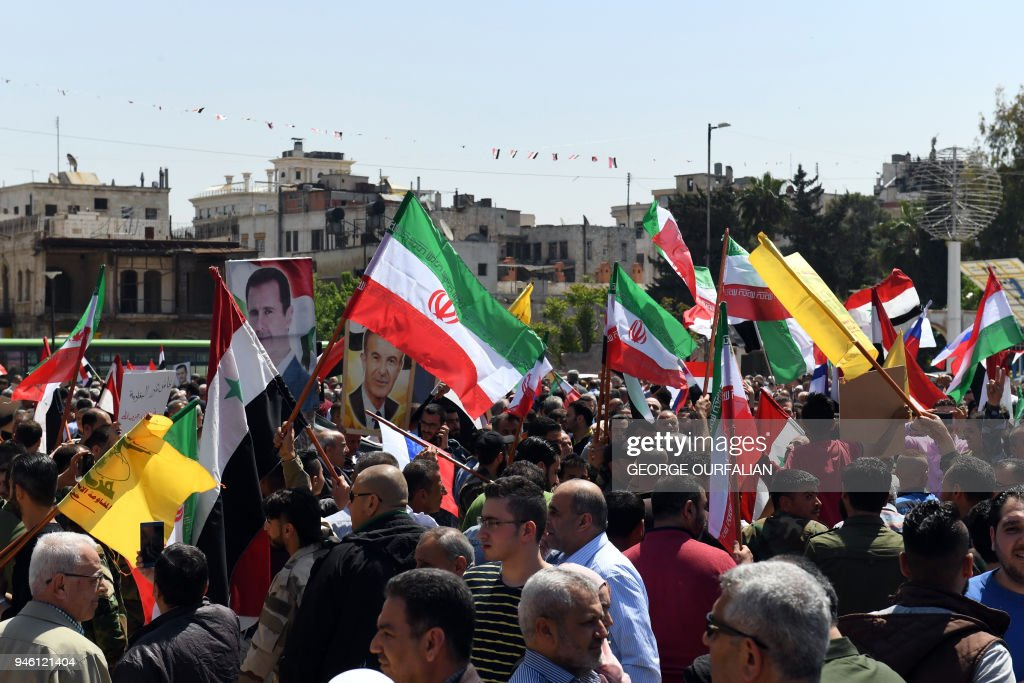Syrians wave the Syrian and Iranian flags and wave portraits of President Bashar al-Assad as they gather in Aleppo's Saadallah al-Jabiri square on April 14, 2018, to condemn the strikes carried out by the United States, Britain and France against the Syrian regime. / AFP PHOTO / George OURFALIAN