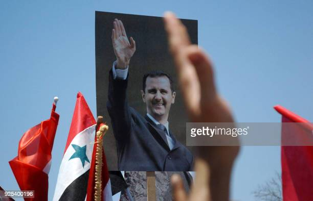 Syrians wave their national flag and hold pictures of President Bashar al-Assad during a rally in his support in Omeyyades Square in Damascus on June...