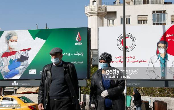 Syrians wearing face masks walk in front of posters informing about the novel coronavirus, in the capital Damascus on April 1, 2020.