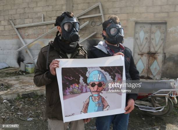 Syrians wearing gas masks hold banners during a protest against United Nations in accuse of their silence to Assad regime forces' chemical gas attack...