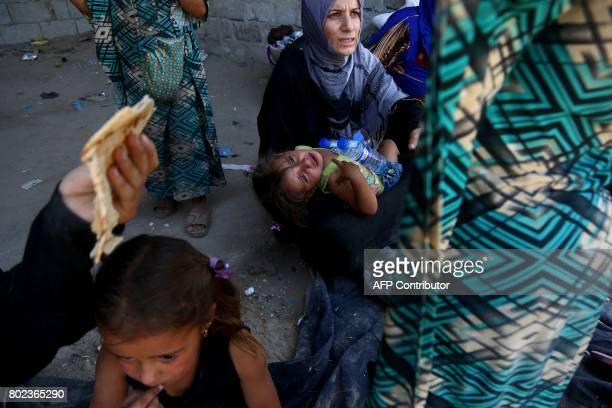 Syrians, who fled areas under the Islamic State group control in Raqa, are seen gathered on June 27, 2017 in the suburb of Jazra on the western city...