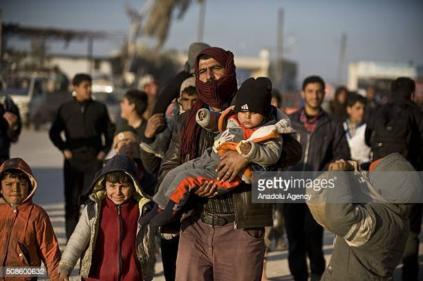 Syrians who fled bombing in Aleppo carry their belongings as they make their way to the Bab alSalam crossing opposite the Turkish province of Kilis...