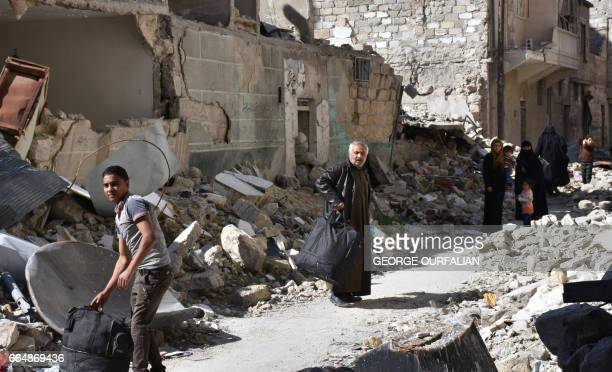 Syrians who fled their hometown due to the fighting carry their belongings upon their return to Aleppo's Myassar neighbourhood on April 5 2017 / AFP...