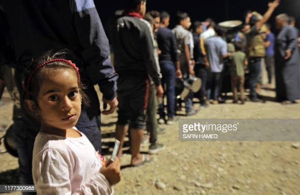 Syrians who have been recently turned refugees by the Turkish military operation in northeastern Syria are pictured upon arriving at the Bardarash...
