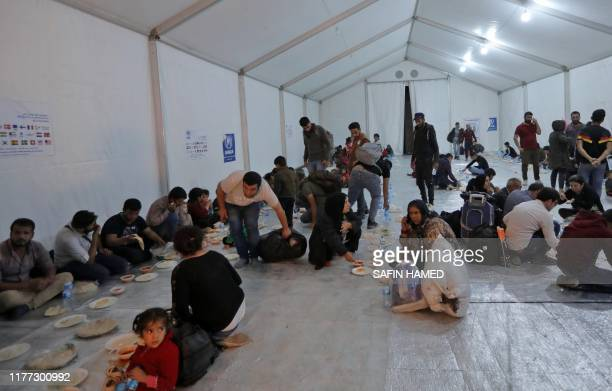 Syrians who have been recently turned refugees by the Turkish military operation in northeastern Syria share a meal in a large tent upon arriving at...