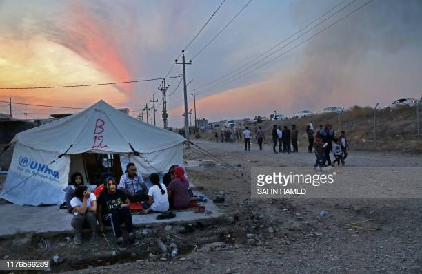 Syrians who have been recentlyturned refugees by the Turkish military operation in northeastern Syria sit together outside a tent at the Bardarash...