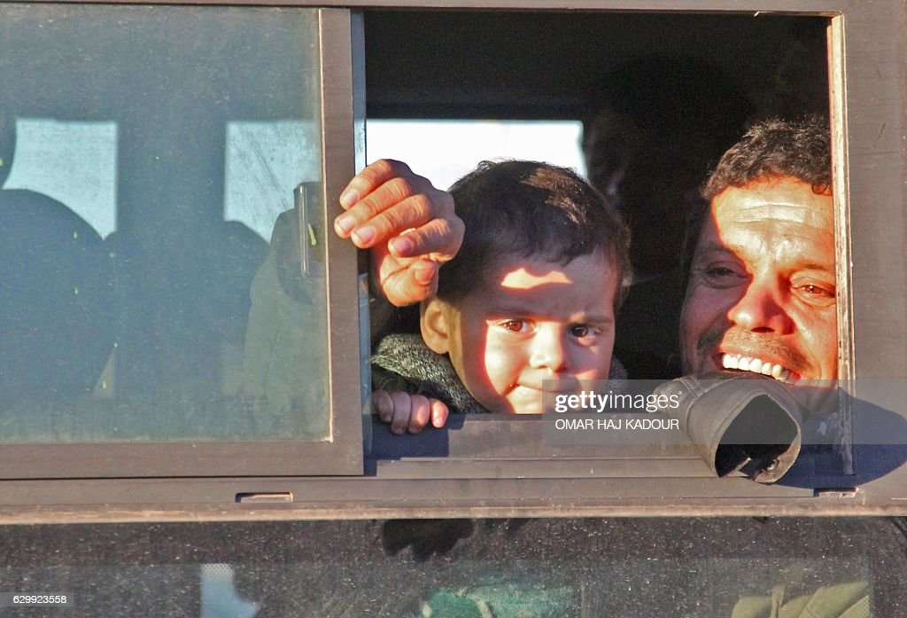 Syrians, who were evacuated from rebel-held neighbourhoods in the embattled city of Aleppo, arrive in the opposition-controlled Khan al-Aassal region, west of the city, on December 15, 2016, the first stop on their trip, where humanitarian groups will transport the civilians to temporary camps on the outskirts of Idlib and the wounded to field hospitals. A convoy carrying the first evacuees from rebel-held parts of Syria's Aleppo arrived in opposition territory west of the city on Thursday, a doctor there and a monitor said. / AFP / Omar haj kadour