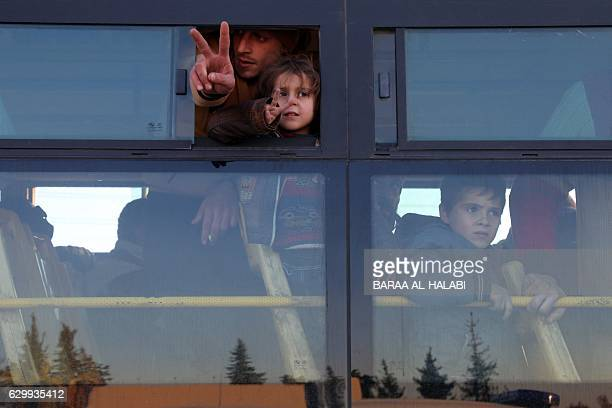 TOPSHOT Syrians who were evacuated from rebelheld neighbourhoods in the embattled city of Aleppo gesture as they arrive in the oppositioncontrolled...