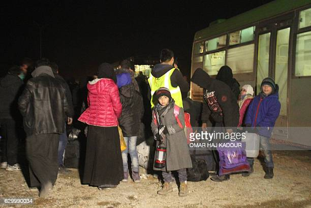 TOPSHOT Syrians who were evacuated from rebelheld neighbourhoods in the embattled city of Aleppo arrive in the oppositioncontrolled Khan alAassal...