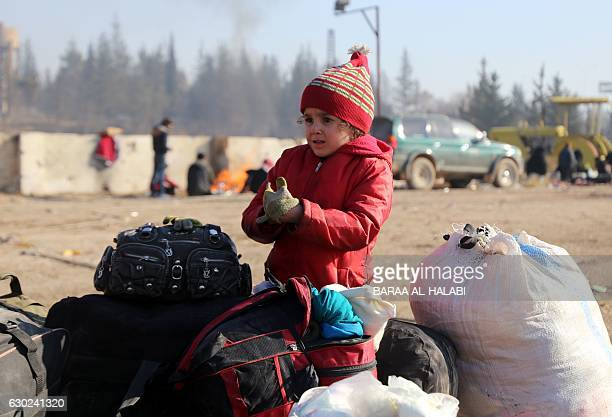 TOPSHOT Syrians who were evacuated from the last rebelheld pockets of Syria's northen city of Aleppo arrive on December 19 2016 in the...