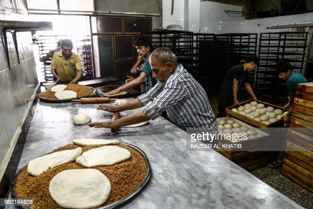 Syrians work in a bakery to prepare Maarouk a sweet pastry usually stuffed with dates or other sweet fillings consumed during the Muslim fasting...