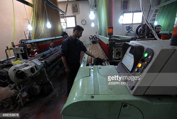 Syrian's work on machines at a rehabilitated textile factory in Aleppo's industrial area in the government controlled side of the wartorn northern...