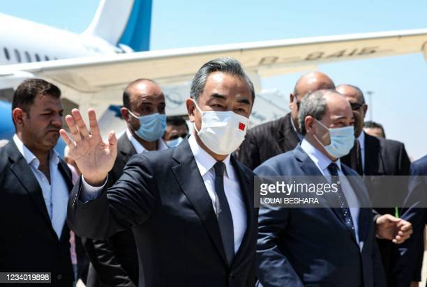 Syria's Foreign Minister Faisal Mekdad receives his Chinese counterpart Wang Yi at the airport in the capital Damascus, on July 17, 2021.